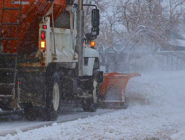 A Carson City snowplow moves snow off of Roop St. on Christmas eve. More than 4 inches of snow had fallen in town as of 5 p.m.