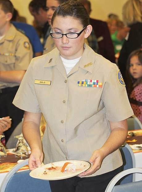 Sarah Inglis, a cadet in the Churchill County High School Junior ROTC program, helps bus the tables as par tof the organization's community service project.