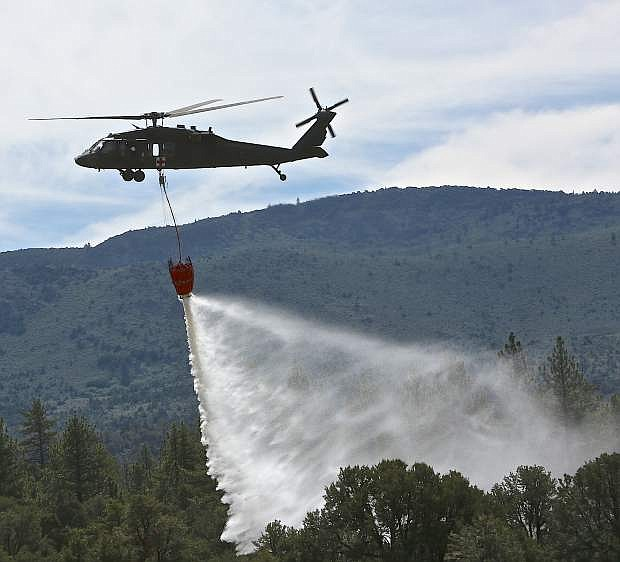 An Army National Guard Blackhawk drops a 660 gallon load of water on a wooded area during fire training Wednesday near Markleeville.