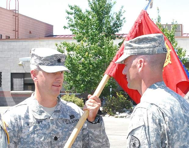Capt. Christopher Yell of  Elko receives the guidon from Lt. Col. Eric Wishart, left, commander of the 757th CBT Sustainment Support Battalion.. Yell became the new commander of the Nevada Army National Guard's  593rd Transportation Company on Saturday.