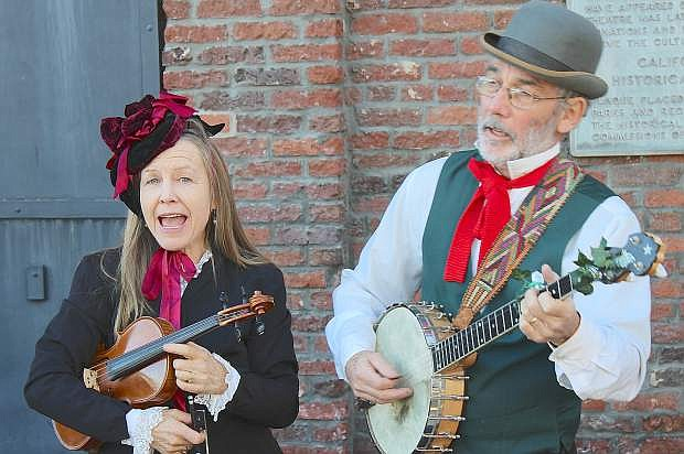 Pamela Kather and Gordy Oligher play traditional Christmas songs and hymns from their sidewalk location at Nevada City's Victorian Christmas.