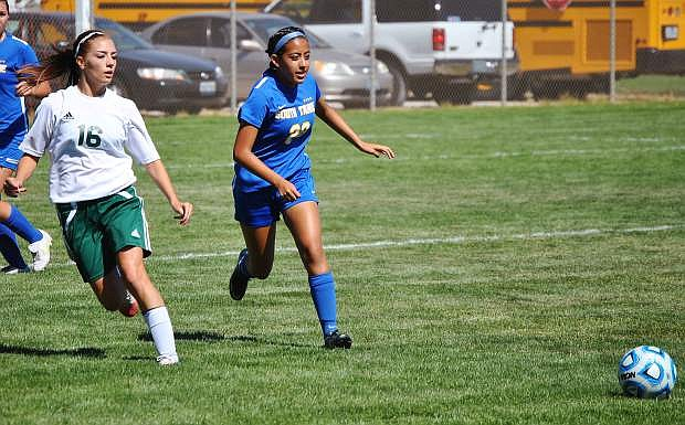 Wave senior Kayla Biggs,left, competing with Vikings senior Stacy Vasquez for control. Mike Sciandra / LVN