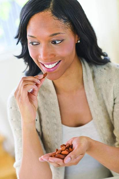 USA, New Jersey, Jersey City, Woman eating almonds