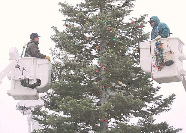 City employees Tanner Humphrey, left, and Kevin Gulley string lights on Fallon's Christmas tree. Toniight's tree lighting begins at 6 p.m.