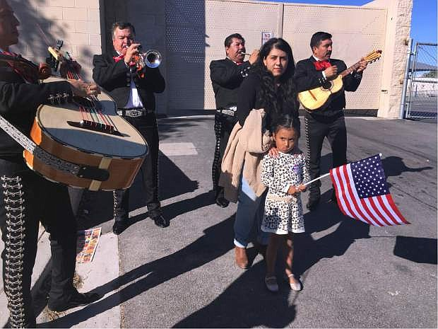 Jacqueline Lima, 20, walks with her four-year-old sister, Karla, holding an American flag, and gets serenaded by a mariachi group after Lima voted for the first time, Tuesday, Nov. 8, 2016, in Las Vegas. Immigrant advocates in Las Vegas worked to get more U.S.-born Latinos to the polls on Election Day as early voter numbers suggest a surge in Hispanic voters. Lima voted for Democrat Hillary Clinton. (AP Photo/Russell Contreras)