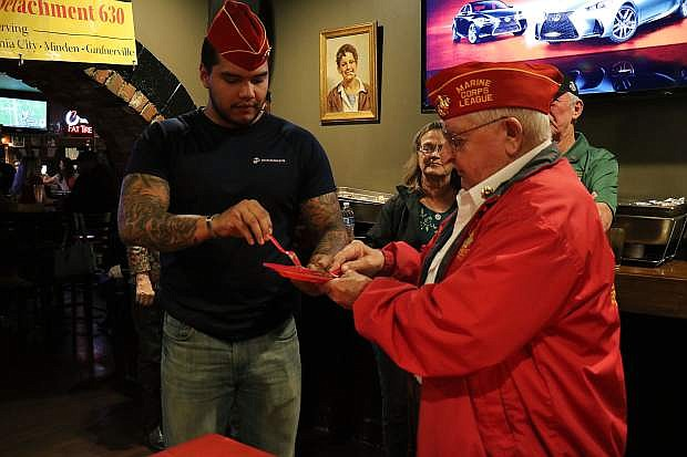 It's a tradition for the oldest veteran marine (Joe Gabiola) to take a bite and pass down a slice to the youngest marine (Martin Rodriguez).