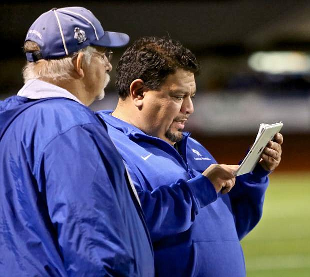 Carson varsity coaches Greg Chech and Vic Castro use an iPad Thursday night to review plays during the Douglas game.