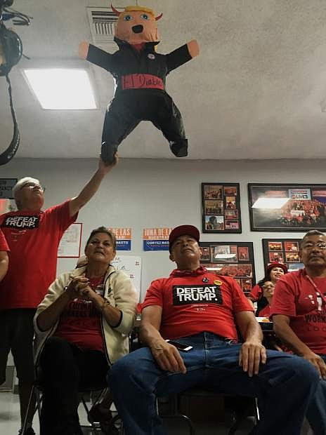 Members of the Culinary Workers Union Local 226, cheer during a rally under a Donald Trump pinata in Las Vegas Monday, Nov. 7, 2016. Voters in swing state Nevada will play an outsized role on Tuesday when they decide whether Hillary Clinton or Donald Trump should get their six coveted electoral votes. The state also has seen a high number of Latinos vote early where Democrat Catherine Cortez Masto is trying to become the nation's first Latina senator. (AP Photo/Russell Contreras)