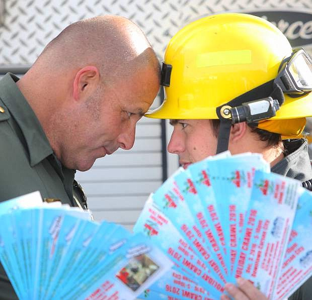 Carson City Sheriff's Deputy Bob Guimont and Carson City Firefighter Dustin Peterson go face to face in a challenge to see which department can sell the most tickets for Holiday Crawl 2016, a community fundraiser to benefit the Holiday with a Hero program.