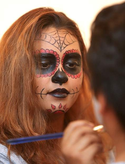 Naidelyn Gomez paints the face of a student at the Day of the Dead celebration on Tuesday at Western Nevada College.