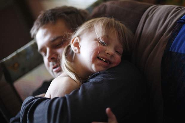 In this Friday, Nov. 4, 2016, photo, Justin Hathaway hugs his daughter Ella, who suffers from Goltz syndrome, a rare illness that requires frequent care from medical specialists, at their home in Tonopah, Nev. Tears well up in the eyes of Ella's mother, lifelong Tonopah resident Acacia Hathaway, as she talks about last year's closure of Nye Regional Medical Center, the only hospital within 100 miles of her home. (Rachel Aston/Las Vegas Review-Journal via AP)