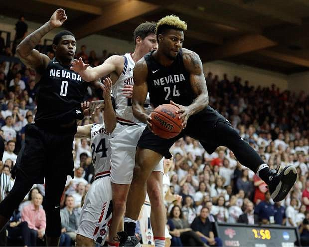 Nevada's Jordan Caroline, right, pulls in a rebound next to Saint Mary's Joe Rahon during the first half of an NCAA college basketball game Friday, Nov. 11, 2016, in Moraga, Calif. At left is Nevada's Cameron Oliver. (AP Photo/Ben Margot)