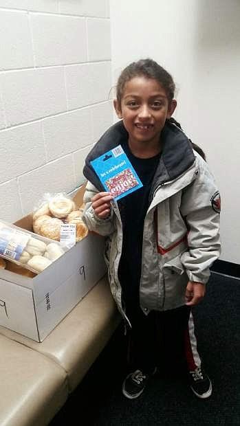 Angel, a third grade student at Mark Twain Elementary School, opens his NHS food basket.