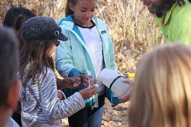 Watershed Specialist Shane Fryer pours some Carson River water into some beakers so students can test for different water quality factors.