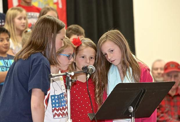 Eleanor Romeo, Leea Waterman, Addysen Davis and Camryn Peachay read about the history of Veterans Day during an assembly at Fritsch Elementary Thursday.