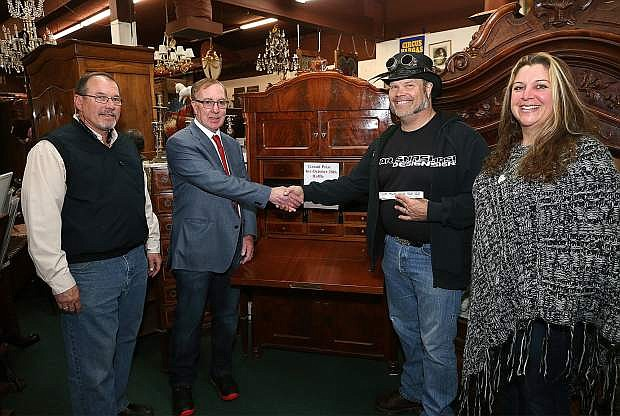 From left, Mike Riggs, president of the Downtown Business Association and Hanifin's Arts and Antiques owner Michael Robbins present Eric and Rebecca Bevans with an antique desk in Carson City, Nev. on Thursday, Nov. 3, 2016. The desk was the grand prize from the raffle in last week's DBA Carson Street celebration.