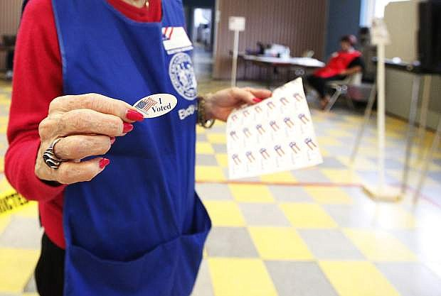 Volunteer handing out I Voted stickers after filling out a election ballot at a district voting station