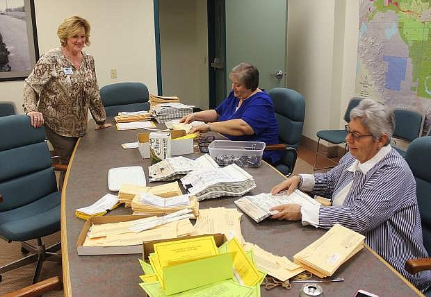 From left, County Clerk Kelly Helton, Renae Paholke and Nyla Howell open absentee envelopes on Thursday. The ballots will be processed on Tuesday.