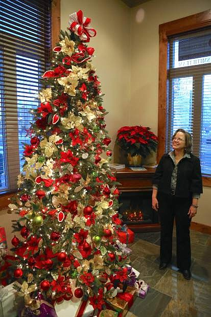 """Marianne Rhoads, a senior paralegal at Rutledge Law Center admires a Christmas tree in their lobby decorated by Carson City resident Charles Adams. Adams, who has photographed many celebreties and was Muhammad Ali's personal photographer, calls his design the """"Magic of Christmas."""""""