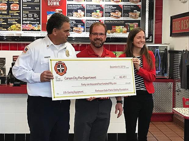Carson City Fire Chief Bob Schreihans accepts a check from Firehouse Subs co-owner Damon Kreizenbeck and Public Safety Foundation Senior Manager of Foundation Programs Jackie Gubbins.