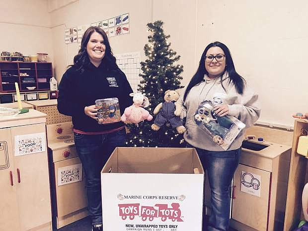Lindsey McElfish, left, and Sierra Fowzer of Carson City Parks and Recreation add toys to the collection bin to benefit Toys for Tots. Drop toys through Dec. 19 at bins located at the Carson City MAC, Community Center, Aquatic Facility, or Ron Wood Family Resource Center.