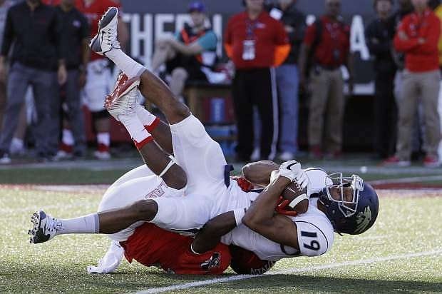 Nevada wide receiver Wyatt Demps catches a pass over UNLV defensive back Darius Mouton during the first half of an NCAA college football game Saturday, Nov. 26, 2016, in Las Vegas. (AP Photo/John Locher)