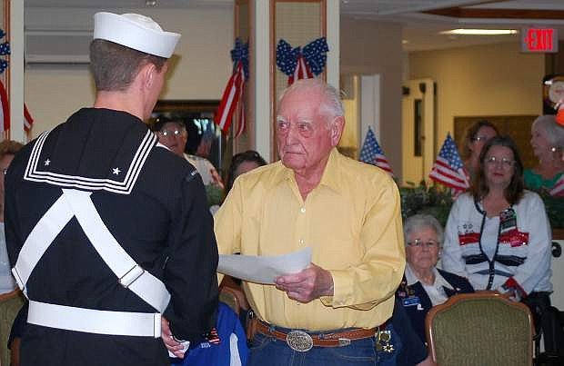 Navy airman Nick Lysne of Naval Air Station Fallon color guard presents a certificate of appreciation to veteran Roland Christiansen during a 2014  veterans recognition program,