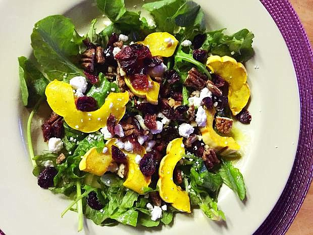 An arugula salad topped with roasted delicata squash and other goodies is a great healthy side for Thanksgiving dinner.