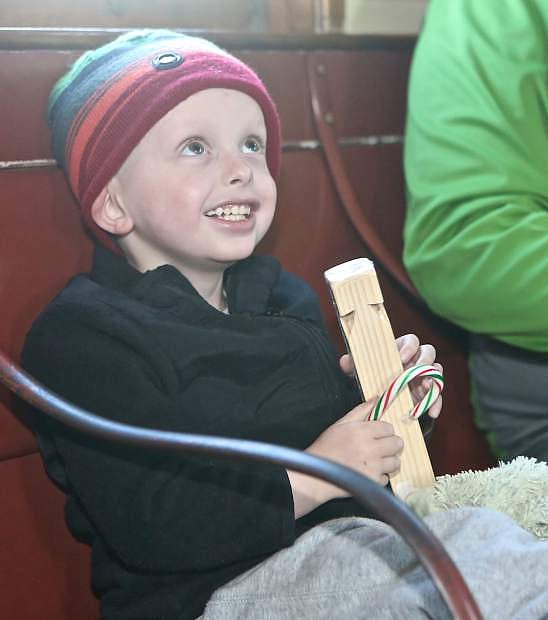 Diagnosed with Neuroblastoma in April 2015, 4-year-old Logan Smith shows a big smile to Santa after receiving a candy cane and train whistle Saturday at the Nevada State Railroad Museum.