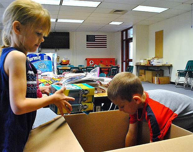 Lahontan Elementary School first-graders Ruth Fisher, 6, left, and Jace Few, 7, pack a box almost as big as they are to send to Nevada Army National Guard units stationed in Kuwait during Christmas.
