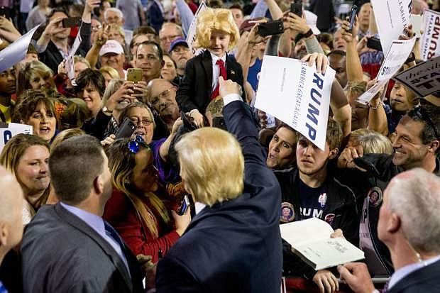 Republican presidential candidate Donald Trump gestures to Colton Jordan, 5, of Cario, Ga., center, who dresses up like Trump following a rally at Valdosta State University in Valdosta, Ga., Monday, Feb. 29, 2016. (AP Photo/Andrew Harnik)