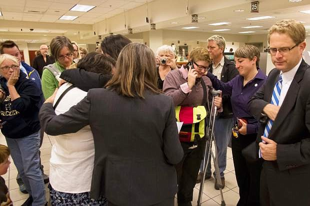 Rachael Beierle, third from right, calls family to tell them she and Amber Beierle, second from right, will not be able to get married on Wednesday, Oct. 8, 2014 at the recorder's office at the Ada County Courthouse in Boise, Idaho.   U.S. Supreme Court Justice Anthony Kennedy has temporarily blocked an appeals court ruling that declared gay marriage legal in the states of Idaho and Nevada. The order came minutes after Idaho on Wednesday filed an emergency request for an immediate stay.  (AP Photo/Otto Kitsinger)