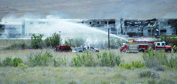 Published Caption: Firefighters from Fallon/Churchill and Naval Air Station Fallon extinguish a fire that engulfed several rail passenger cars on June 24, 2011. The National Transportation Safety Board conducted a hearing on Tuesday and cited three probable causes for the accident and loss of life.
