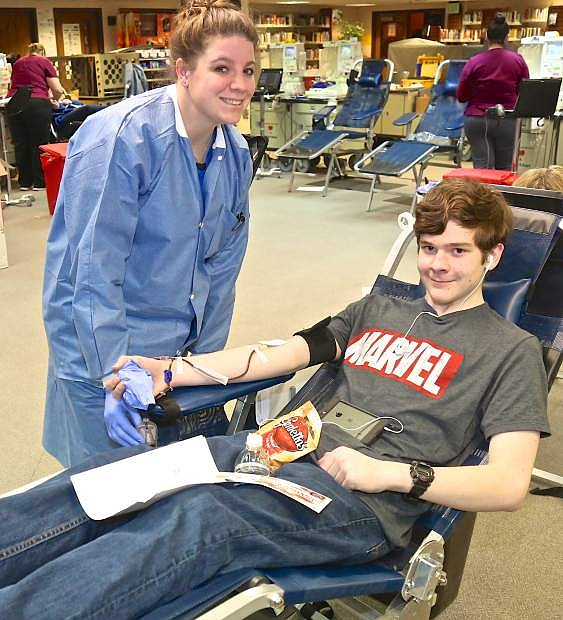 United Blood Services' Amanda Moreno checks on Carson High junior Logan Smedes as he gives blood Wednesday afternoon in the CHS library.
