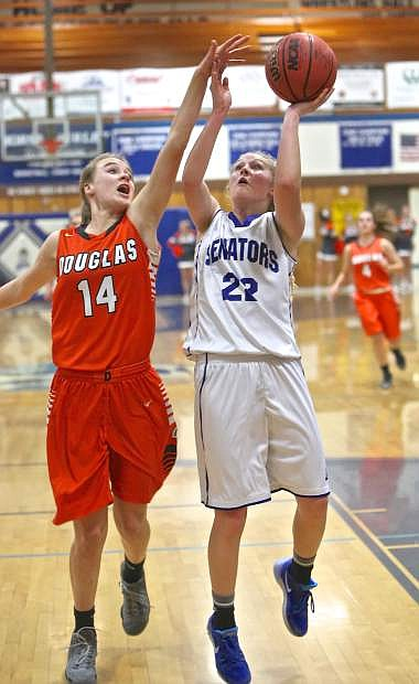 Carson's Lauren Lemburg drives to the hoop against Douglas' Madison Smalley Friday night at Morse Burley Gym.