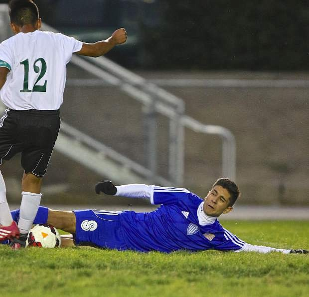 Carson's Alejandro Gonzalez slides to steal the ball from a Hug player Wednesday night in Reno.