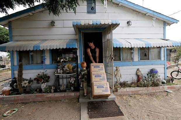In this July 2, 2015 photo, Billy Dunlap, 21, hauls in boxes of bottled water as his son, Brandon, 3, walks alongside at their home in the community of Okieville on the outskirts of Tulare, Calif. Four generations of Dunlaps share the white house with blue trim Christine Dunlap's father-in-law built in the 1940s, and little changed in all those years, until her 170-foot well ran dry in February. (AP Photo/Gregory Bull)