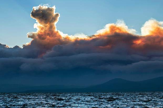 This Wednesday, Sept. 17, 2014 photo shows smoke from a California wildfire rising behind Lake Tahoe as seen from the Nevada side of the lake near Incline Village, Nev. Higher humidity Friday helped slow the growth of the massive Northern California wildfire that authorities say was set deliberately and has forced some 2,800 people to evacuate. (AP Photo/Steve Ellsworth)