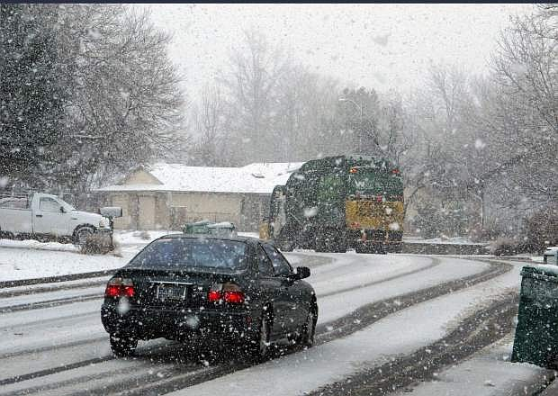 Snowflakes fall as a car follows a garbage truck down a residential street in Sparks on Friday. The Reno-Sparks area is expected to get up to eight inches of snow through the weekend. As much as another six feet of new snow is possible in the upper elevations of the Sierra Nevada, where a winter storm warning continues into Monday.