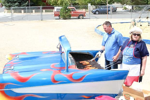 Vice Principal Mark Bacon and reading tutor Hazel Elliot cook hot dogs on a custom bbq donated by Karson Kuston Kruzers for the Empire Elementary anniversary party.