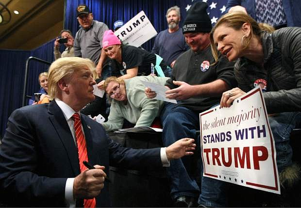 People greet Republican presidential candidate Donald Trump, left, after he spoke at a rally in Reno, Nev., Sunday, Jan. 10, 2016. (AP Photo/Lance Iversen)