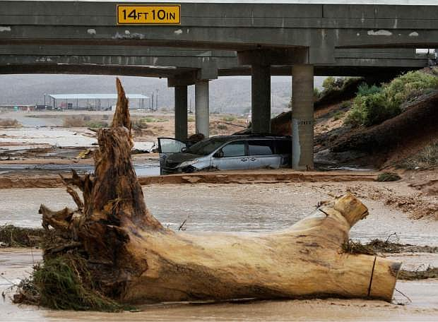 A minivan is seen in floodwaters beneath Interstate 15 in Moapa, Nev., Monday, Sept. 8, 2014. The National Weather Service has issued a flash flood emergency for the area. (AP Photo/John Locher)