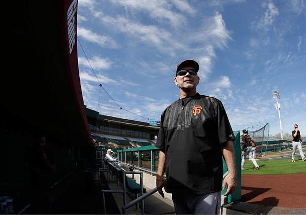 San Francisco Giants manager Bruce Bochy talks with fans as he leaves the field following a spring training baseball practice Thursday in Scottsdale, Ariz.