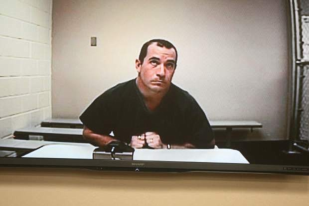 David Gomez, appearing on the video monitor, listens to Judge Tom Perkins on April 9. Gomez denied all charges against him and sought three separate trials.