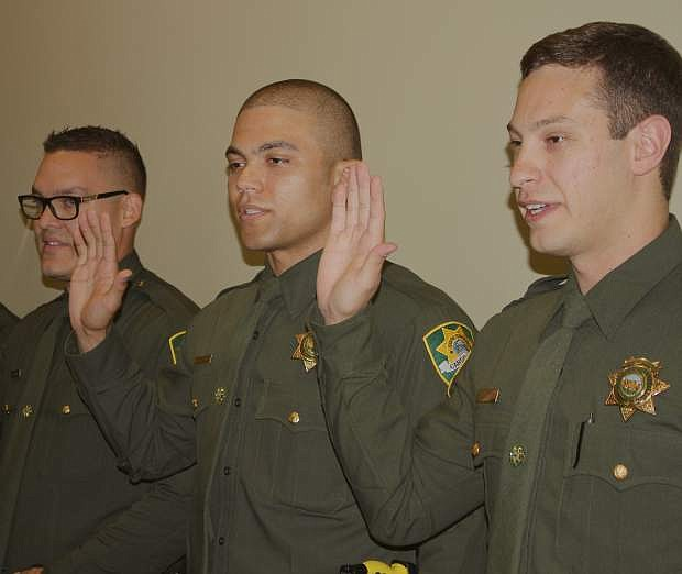 Jeremy Garcia, Daniel Reece and Randy Watkins raise their hands as they are sworn in after the Reserve graduation Friday.