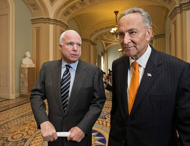 """Sen. John McCain, R-Ariz., left, and Sen. Charles Schumer, D-N.Y., right, two of the authors of the immigration reform bill crafted by the Senate's bipartisan """"Gang of Eight,"""" confer on Capitol Hill in Washington, Thursday, June 27, 2013, prior to the final vote. The historic legislation would dramatically remake the U.S. immigration system and require a tough new focus on border security.  (AP Photo/J. Scott Applewhite)"""