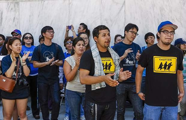 Immigrant students join a coalition of immigrant rights supporters on a 24-hour vigil calling on the U.S. Congress to pass immigration reform outside the Federal Building in Los Angeles Thursday, June 27, 2013. The Senate moved with uncommon bipartisanship Thursday to the brink of passage of legislation offering the priceless hope of citizenship to millions of immigrants living illegally in America's shadows, while also promising a military-style effort to secure the long-porous border with Mexico. (AP Photo/Damian Dovarganes)