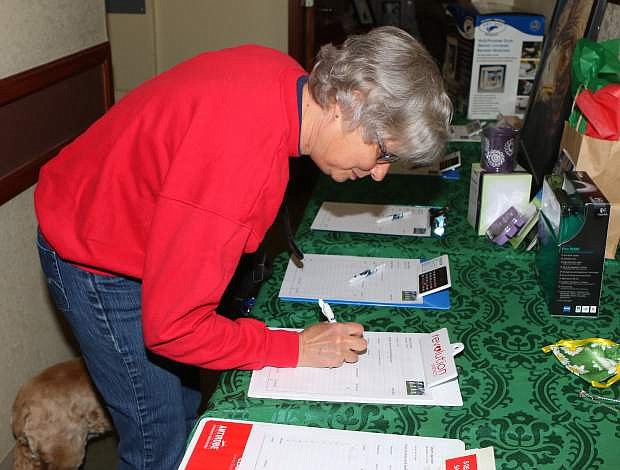 Kathy Graff puts in a silent auction bid at Sierra Veterinary Hospital's fundraiser on Saturday.