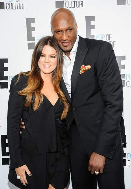 "FILE - In this April 30, 2012 file photo, Khloe Kardashian Odom and Lamar Odom from the show ""Keeping Up With The Kardashians"" attend an E! Network upfront event in New York. Odom, the former NBA star and reality TV personality embraced by teammates and fans alike for his humble approach to fame, was hospitalized and his estranged wife Khloe Kardashian is by his side, after being found unresponsive in a Nevada brothel where he had been staying for days. (AP Photo/Evan Agostini, File)"