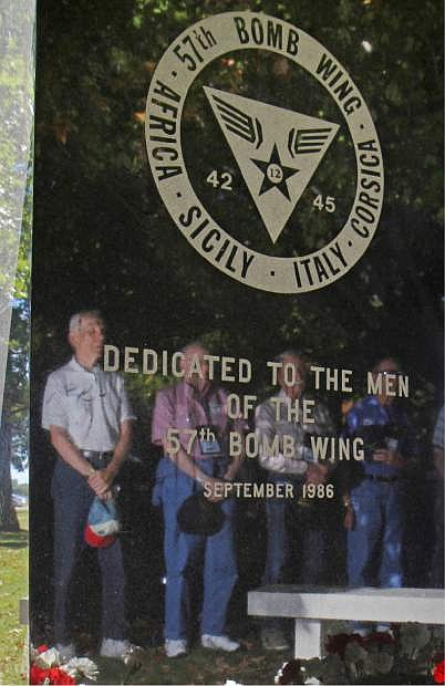 In this Sept. 27, 2013 photo, World War II veterans from the 57th Bomb Wing are reflected in the stone memorial to the wing during a reunion outside the U.S. Air Force Museum at Wright Patterson Air Force base in Dayton, Ohio. As many as 11,000 people served in the 57th that flew missions over German-held Europe from North Africa and the island of Corsica during most of the war. Hundreds survive, according to wing historians and reunion organizers. (AP Photo/Tom Uhlman)
